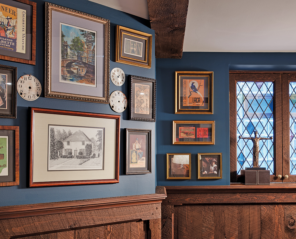 A wall decorated with old photos and antique clock faces.
