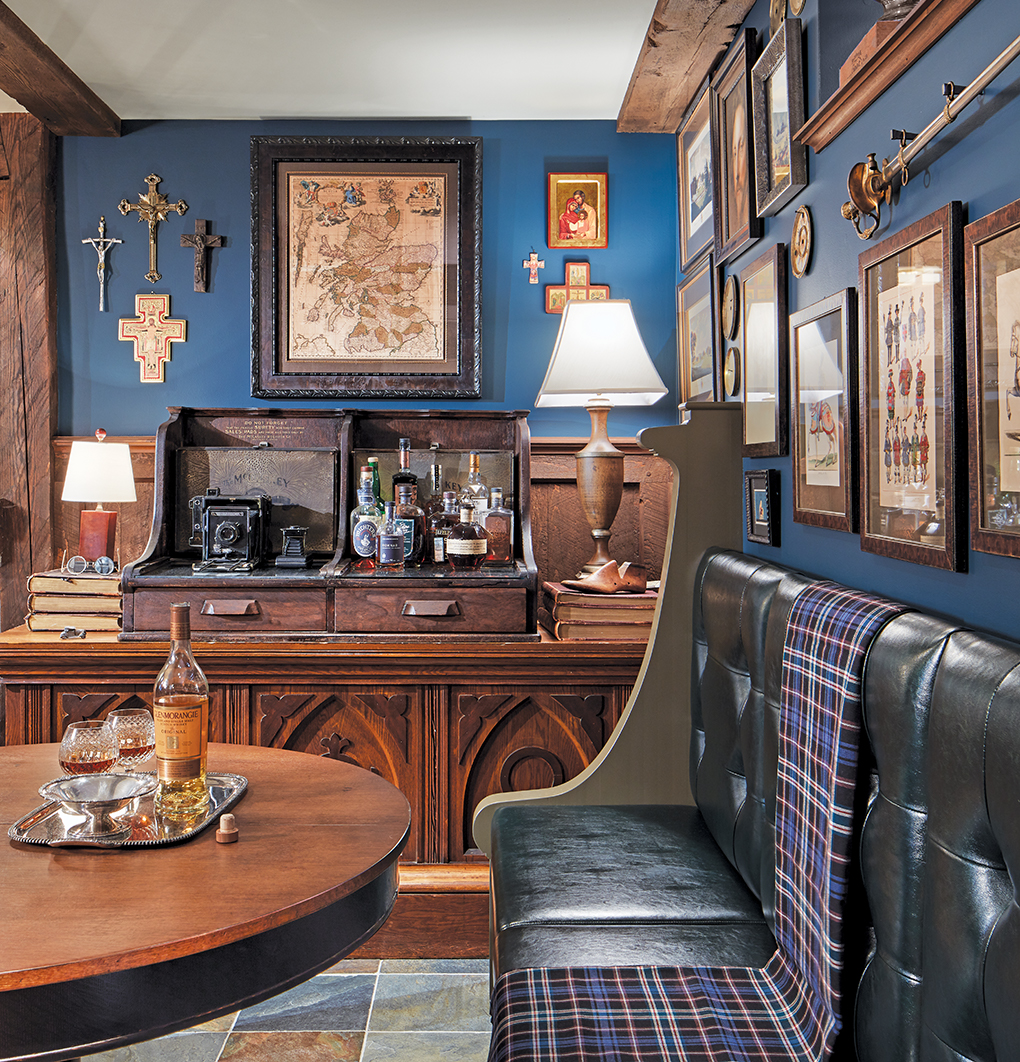 A Scottish-themed basement includes a repurposed church pew and altar, sword, vintage clock-face and coin collections, and large framed antique map of Scotland.