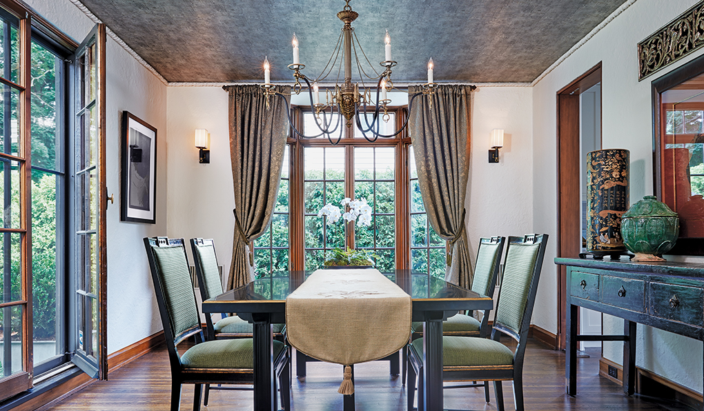 An elegant dining room shows windows surrounding a table and chairs set underneath an ornate chandelier.