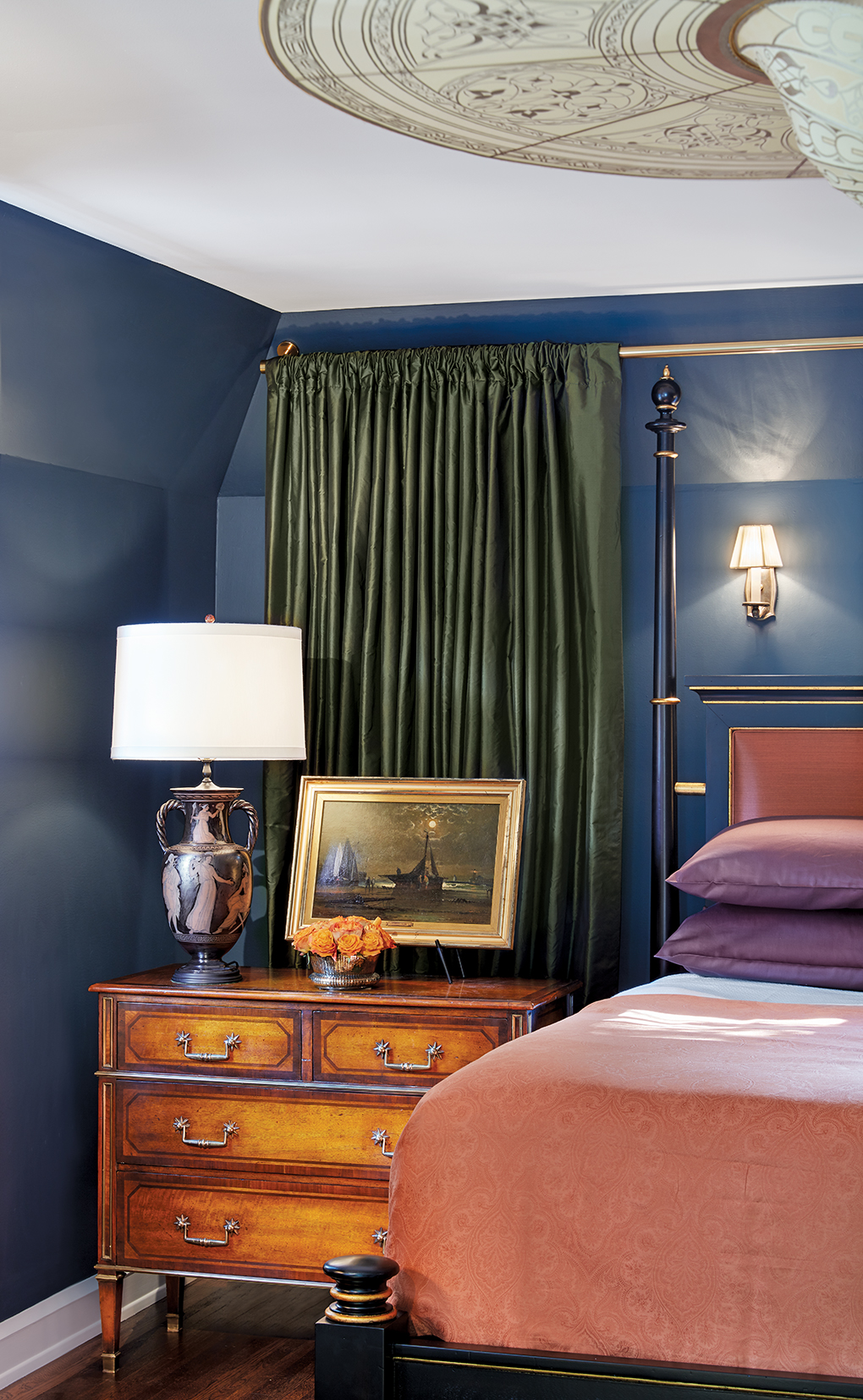 A master bedroom complete with deep navy walls, a Fortuny light overhead.