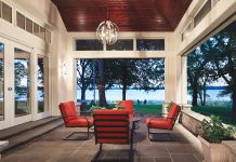 A semi-outdoor patio features a table and chairs, clerestory windows and large pocket doors with Phantom screens that look out onto a lake.