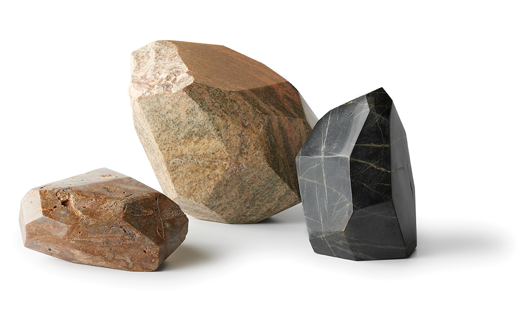 Three rock sculptures, one brown, one beige and one charcoal.