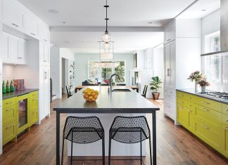 A kitchen with bold white and green cabinetry features a center island with surrounding chairs.