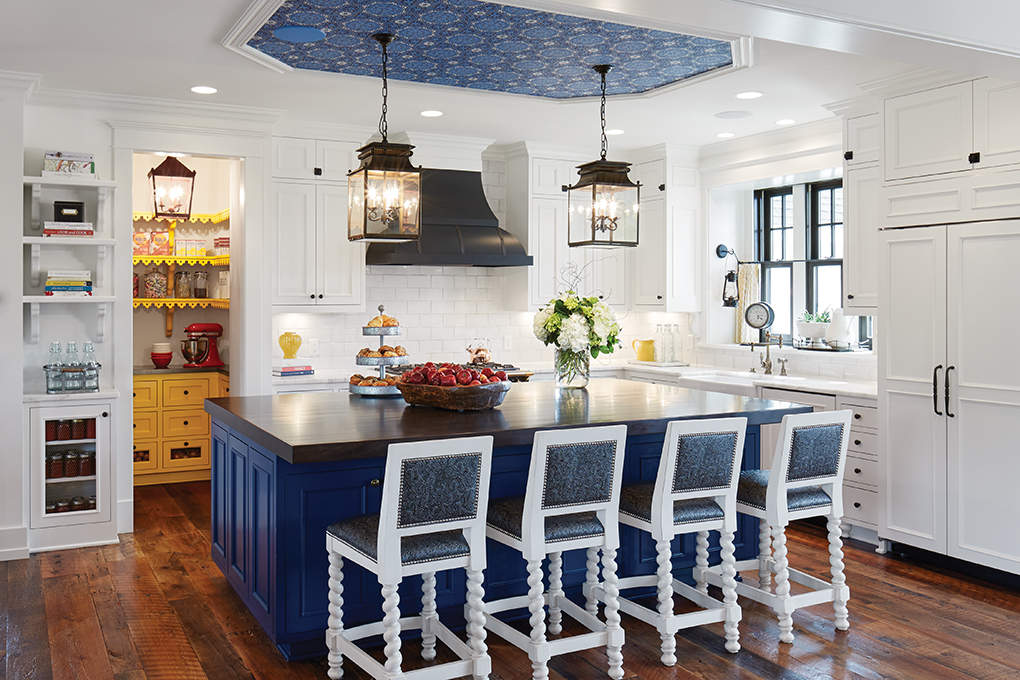 A white kitchen features a subway tile backsplash, blue island and blue wallpaper overhead.