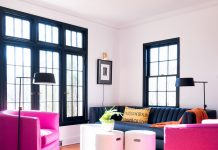 A living room furnished with a couch, footstools, and two pink chairs to add a pink design element.