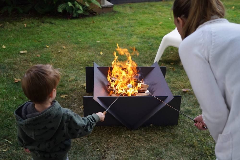 A geometric fire pit with a family roasting marshmallows.