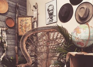 Empty brown woven chair surrounded by plant and hats