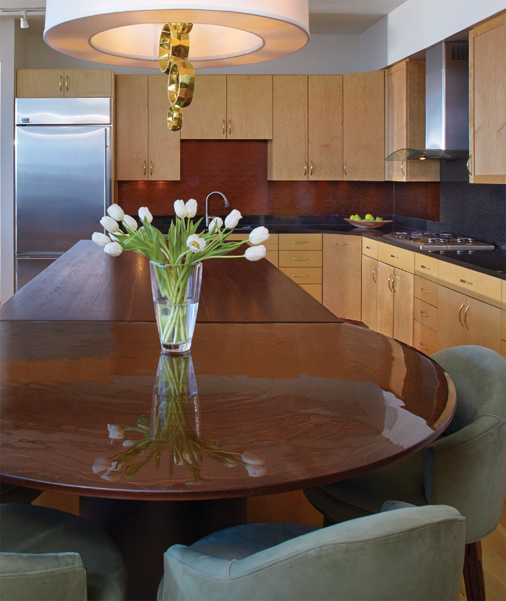 Kitchen and dining with dark wood tables and light wood cabinet space with stainless steel fridge