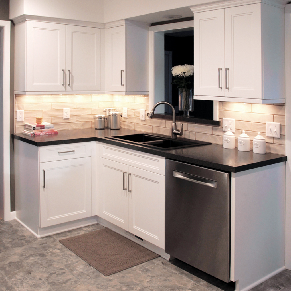 White cabinets with white brick backsplash and stainless steel dishwasher
