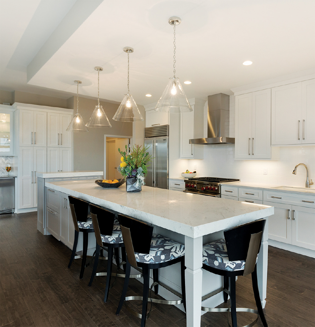 A kitchen with all white cabinetry, stainless steel appliances, center island with surrounding stools and dark, hardwood flooring by Ispiri Design-Build, a winner of the National Kitchen and Bath Association Minnesota Design Awards.