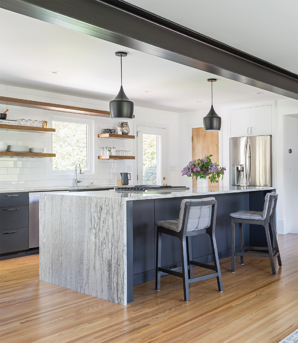 Light hardwood floors, marble kitchen island, black hanging pendant lights, black barstools with gray cushions