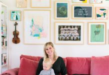 Kate Duininck holds her baby and dog on couch in her Excelsior Home