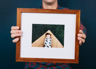 A person holding a newly framed picture from Framebridge.