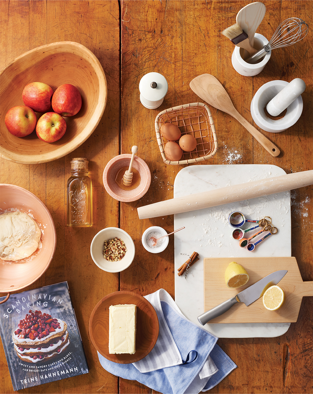 A wooden table full of holiday gift ideas for the kitchen, including a French rolling pin, honey, spatula, ceramic and marble bowls, and more.