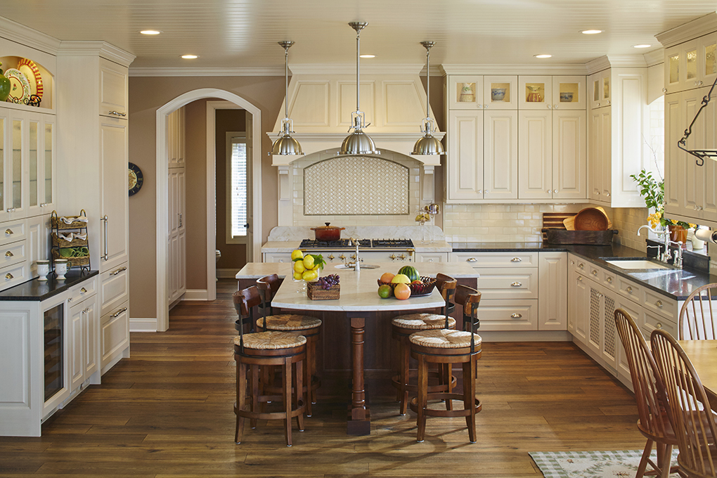An ornate kitchen with cream-colored cabinetry, large range hood, hardwood flooring, center island with surrounding stools, and stone countertops.