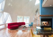 A great room with geometric-patterned windows, fireplace, large red sofa and spiral staircase.
