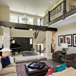 A living room with an exposed beam and loft built by Boyer Building Corporation.