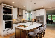 Photo of a kitchen with stainless steel appliances and bar stools at counter