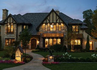 The exterior of a large home with large windows and lawn at night built by Erotas Custom Building.