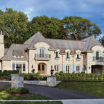 The exterior of a large stone home built by John Kraemer & Sons.