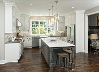 An all white kitchen with dark wood floors built by Knight Construction Design, Inc.