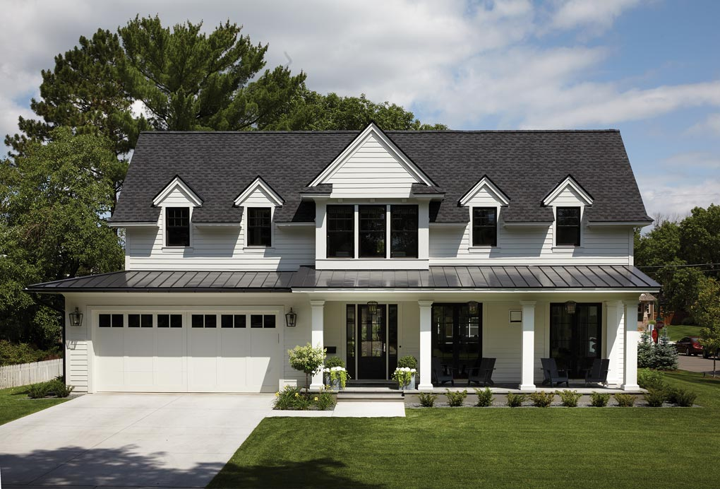 The exterior of a modern white farmhouse.