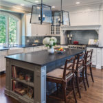 Kitchen with brown barstools and dark countertop and white cabinets