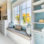 Walk in closet with bench, blue walls, windows
