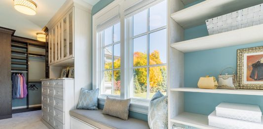 Walk in closet with bench, blue walls, windows