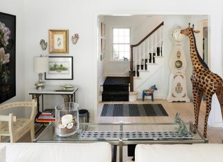 A living room full of random treasures including a three-legged chair, clock and wooden giraffe.