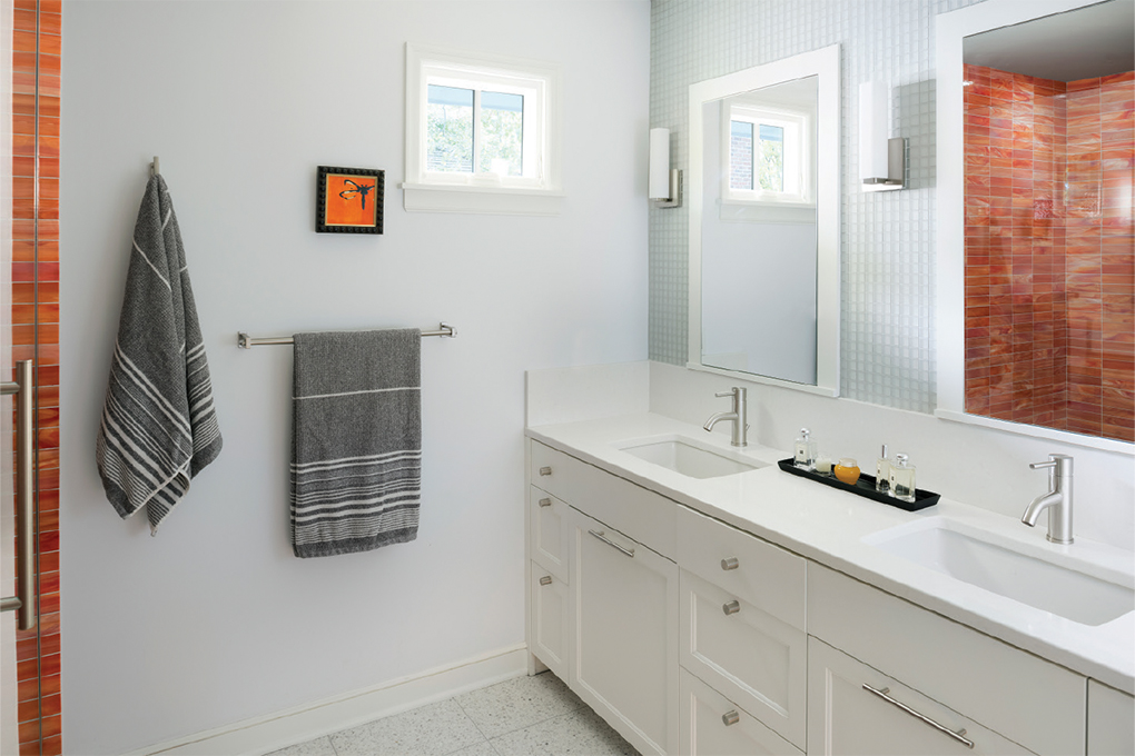 An all white bathroom pops with orange, glass tiles in the shower.