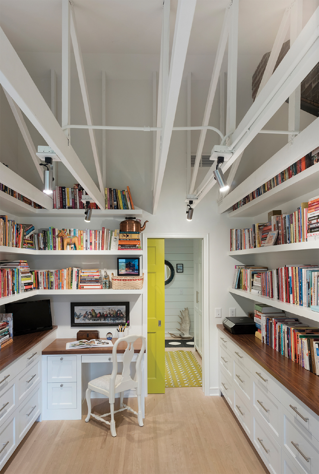 Exposed rafters and brick tower above the book-lined walls of the new office space. The charteuse-painted pocket door opens to a laundry/mudroom.