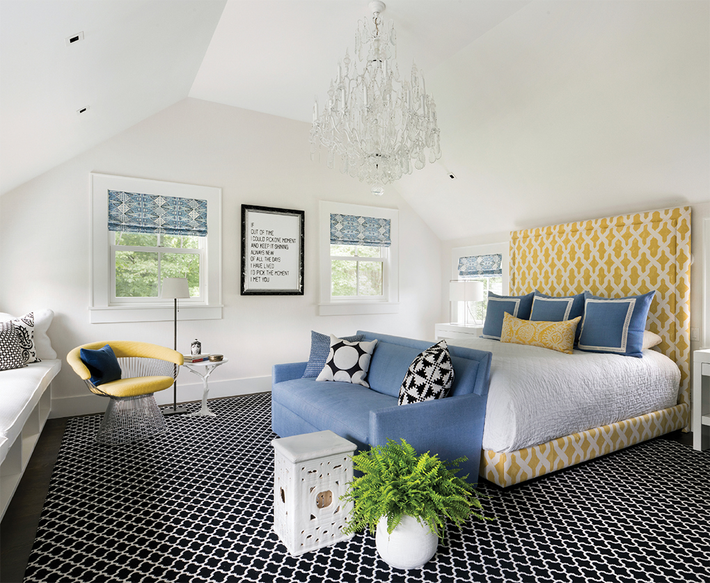 A master bedroom with a large bed, seating and stylish rug.