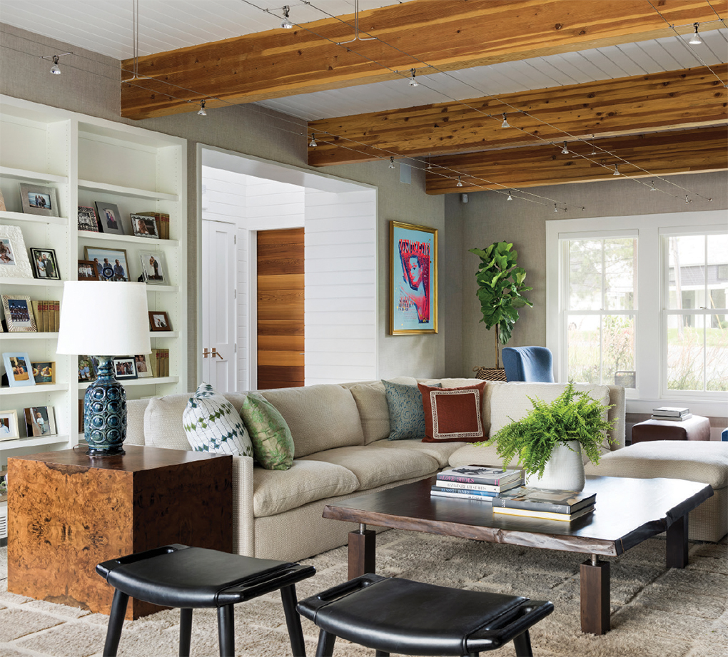 A large family room with seating, a table and exposed wooden beams.