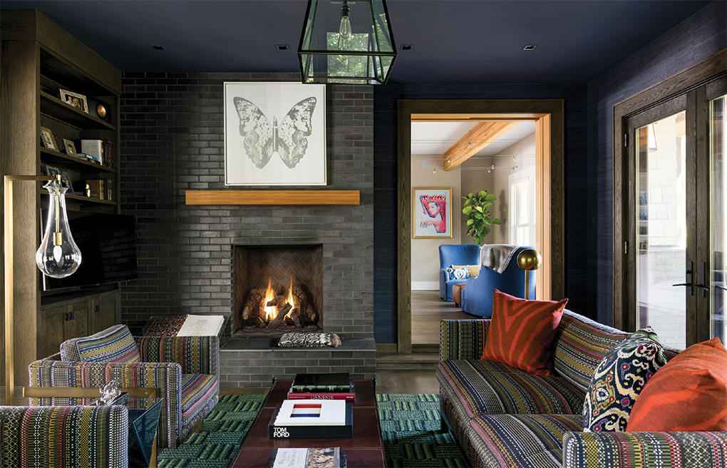 A darkly colored den with brick fireplace, coffee table and seating.