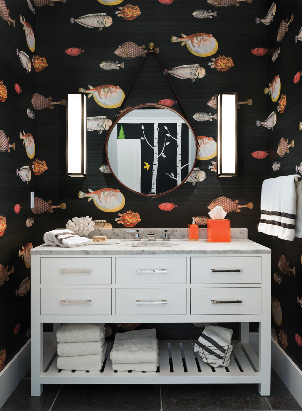 A nautical bathroom with fish wallpaper.