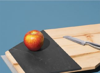 A cutting board by Tandem Made with an apple and knife resting on it.