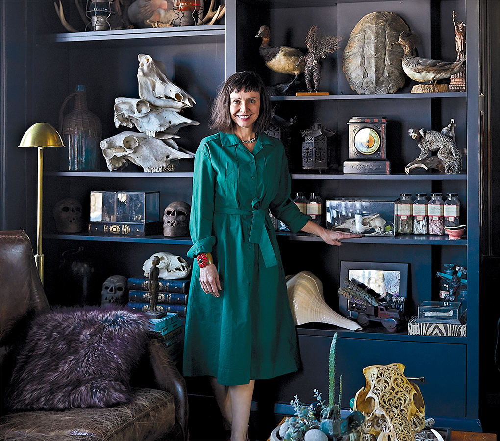 A photo of Christine Ward, owner of Patina, standing next to a shelf full of taxidermy and other collectibles in her home in a green dress.