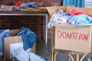 Donation box with clothing on wooden chair
