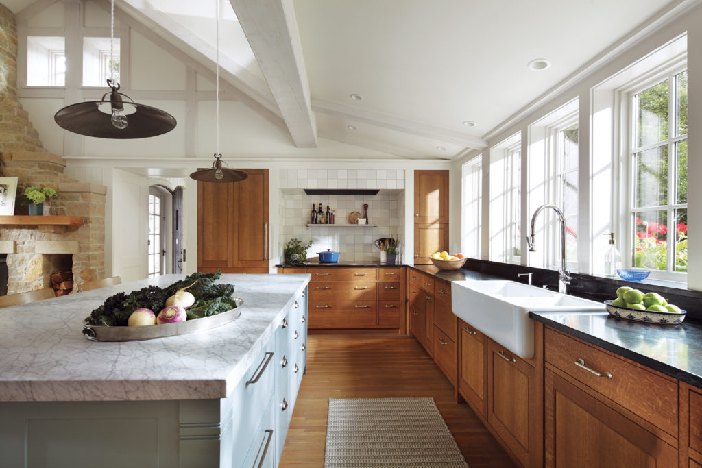 A kitchen in a remodeled home by Albertsson Hansen Architecture features matte-finished quarter-sawn oak cabinets, a farmhouse sink, and a large marble-topped island.