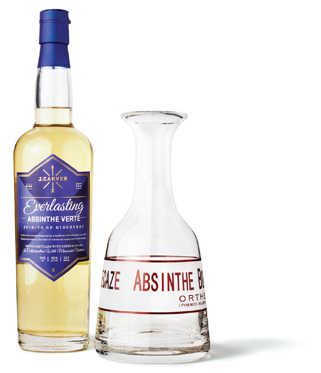A bottle of J. Carver Everlasting Absinthe Verte next to an empty glass.