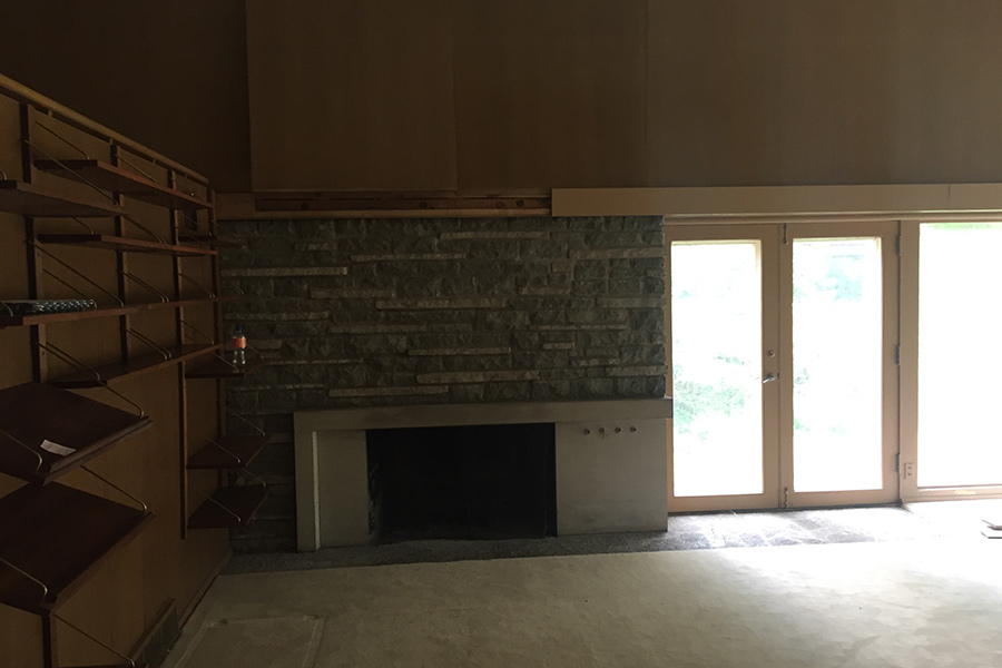"""A """"before"""" photo of a living room with a fireplace before it was remodeled by Bella Custom Homes."""