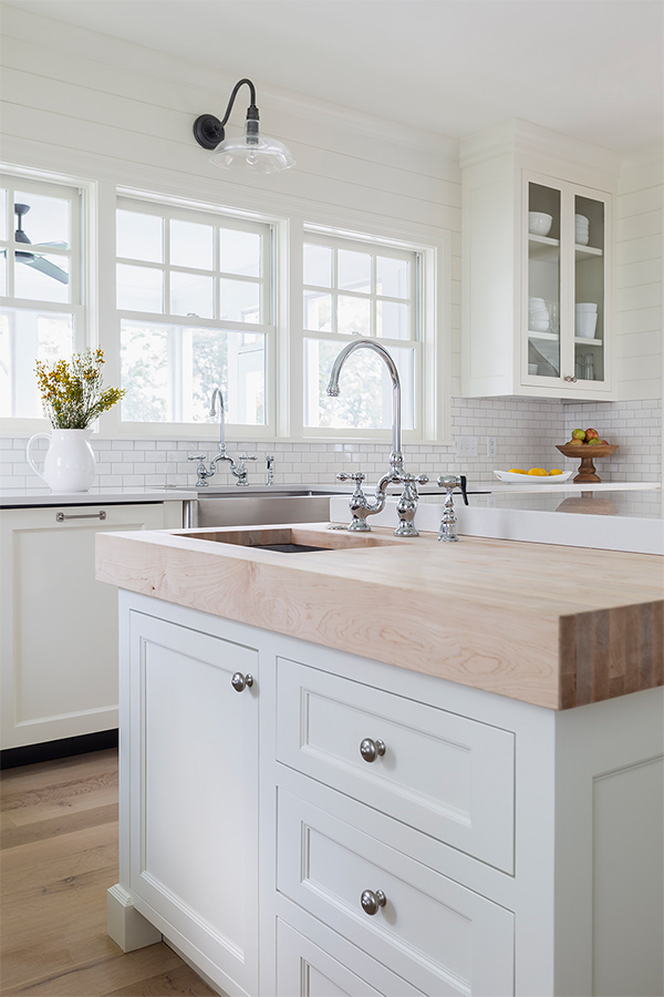 A butcher block in an all white kitchen.