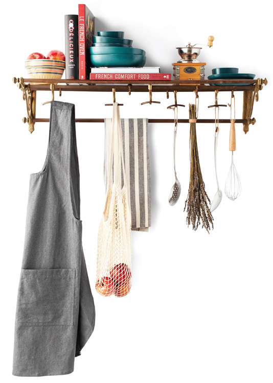 A collection of kitchen items and utensils hanging from a rack.