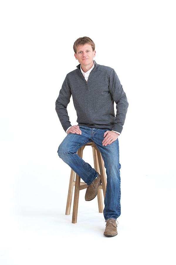 Photo of a man sitting on a wooden stool