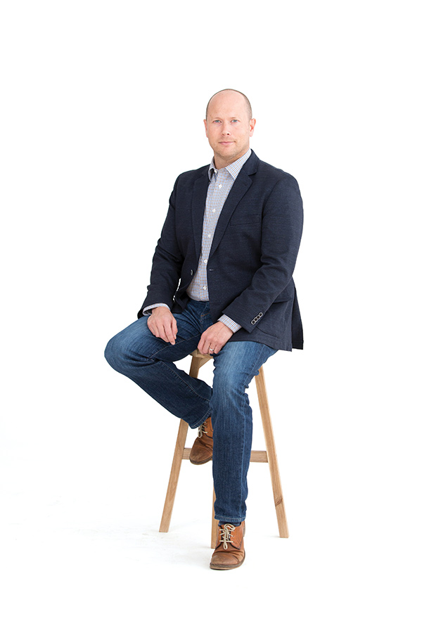 Photo of a man on a wooden stool