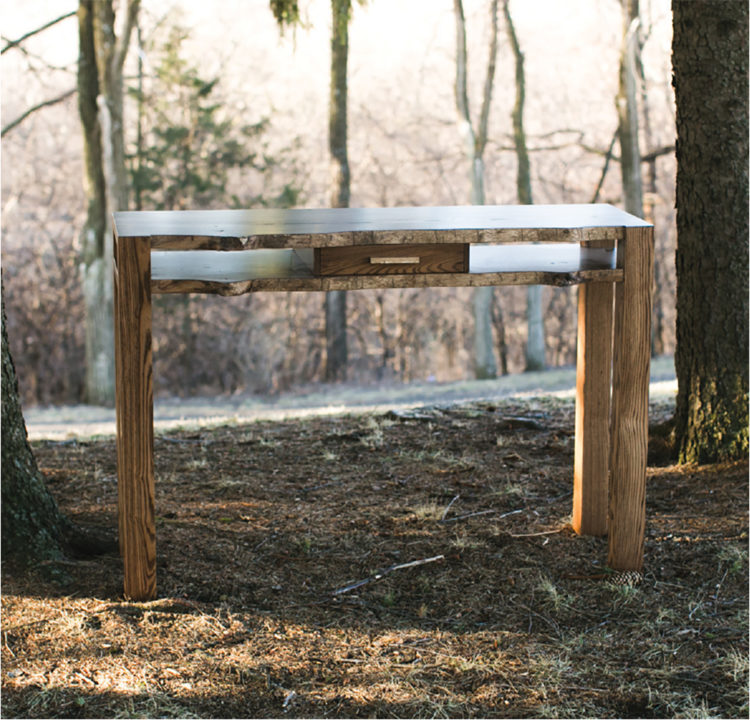 A wooden table next to some trees crafted by Grant Kaihoi