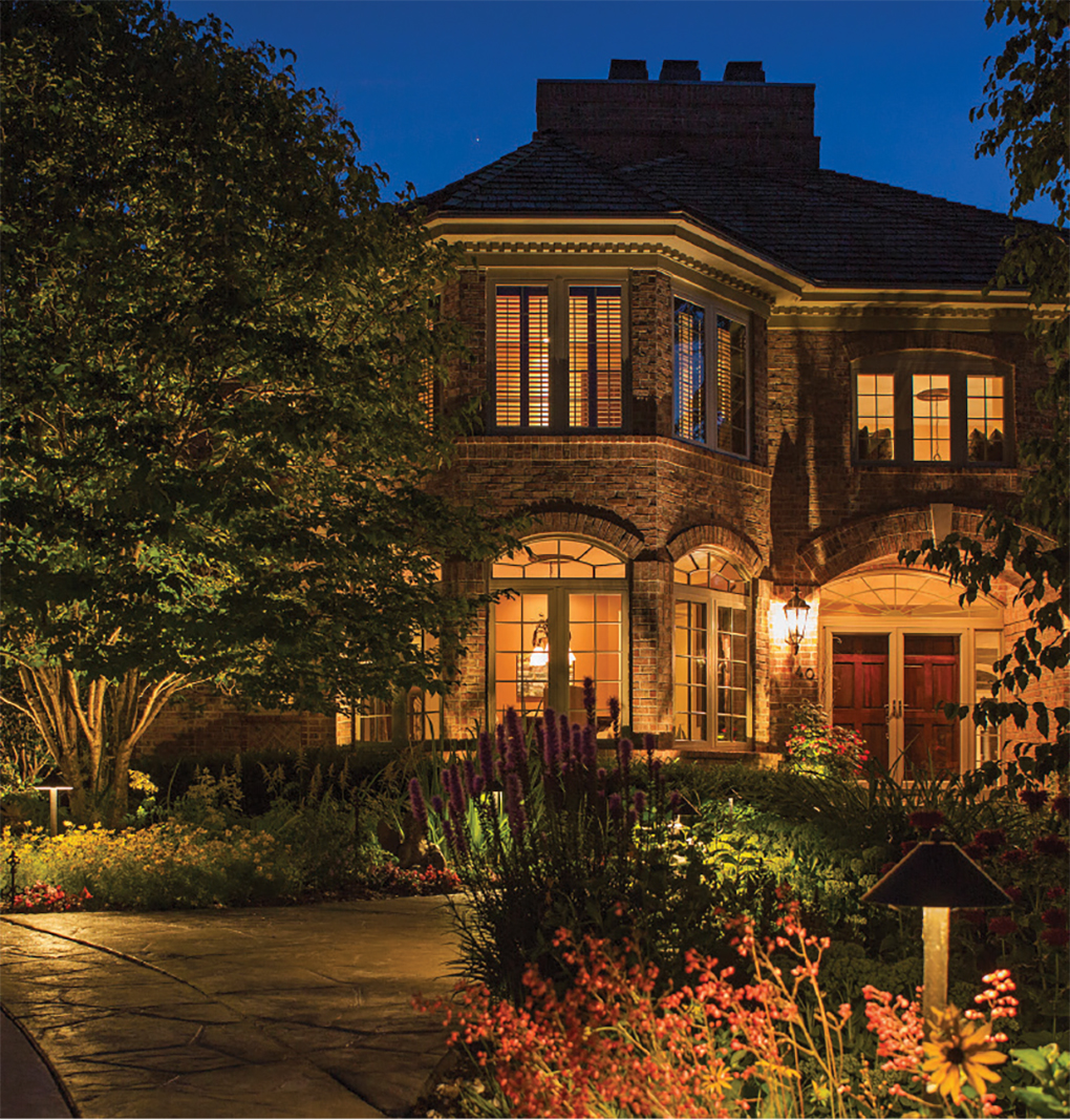 A stately home lit up at night thanks to Erickson Outdoor Lighting.