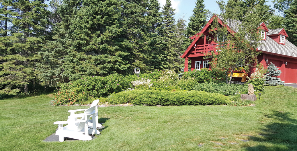 A red timber-frame Lundie cabin with a large yard.