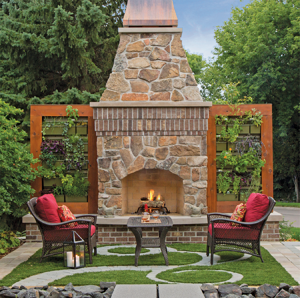 Living walls of herbs and vegetables frame the outdoor fireplace.